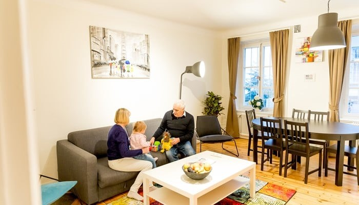 standard two bedroom apartment - family with a kid on the sofa - stockholm city center apartment hotel ApartDirect Sveavägen