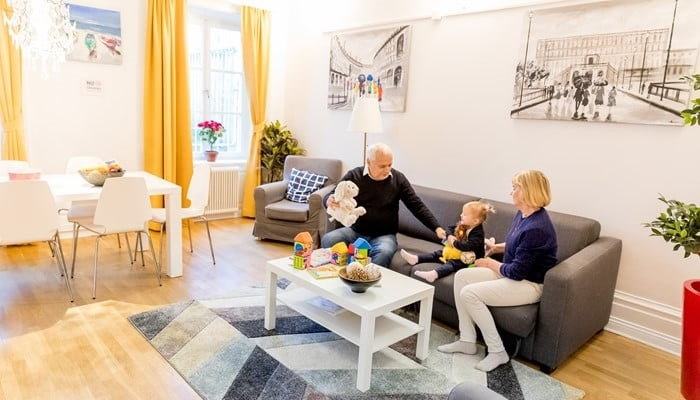 vacation apartments sveavägen stockholm: small two bedroom apartment - family playing with a kid in living room