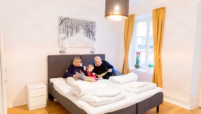 holiday partments sveavägen stockholm: small two bedroom apartment - family with a kid reading a book in the bedroom